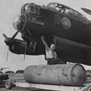 Preparing to bomb-up a Lancaster of No. 460 Squadron, armourer Cpl W. E. Dawson rides a 4,000lb high-capacity bomb (a 'Cookie'), while behind is a portion of the incendiary bomb containers which made up the normal load for area attacks, September 1943.