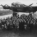 Squadron crews of mainly 'C' Flight lined up in front of 'A2' Aussie, March 1944. Vic Neale and crew, front right hand corner. In the background the station commanders, Group Captain, Hughie Edwards car or the car of the squadron commander, Wing Commander, H.D. Marsh.