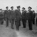 "Final Parade inspection of 460 squadron ""Menzie's Blue Orchids"", nicknamed by the Army, but very proud to wear the uniform, led by Air Vice Marshal Wrigley C/O. RAAF England, followed by Squadron Commander Wing Commander Swann, DSO, DFC, then Wing Commander Frank Lawrence, DFC, DFM and other distinguished officers, East Kirkby 460 Squadron October, 1945."